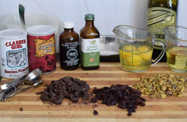A cutting board showing the ingredients for Chocolate Cherry Biscotti with Pistachio.