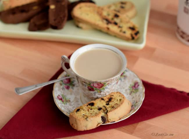 Chocolate Cherry Biscotti with Pistachio on a plate with a cup of coffee.