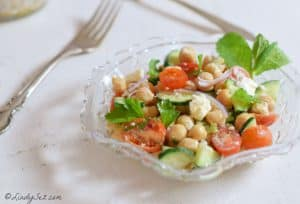A.glass bowl with Chickpea Salad filled with bright veggies.