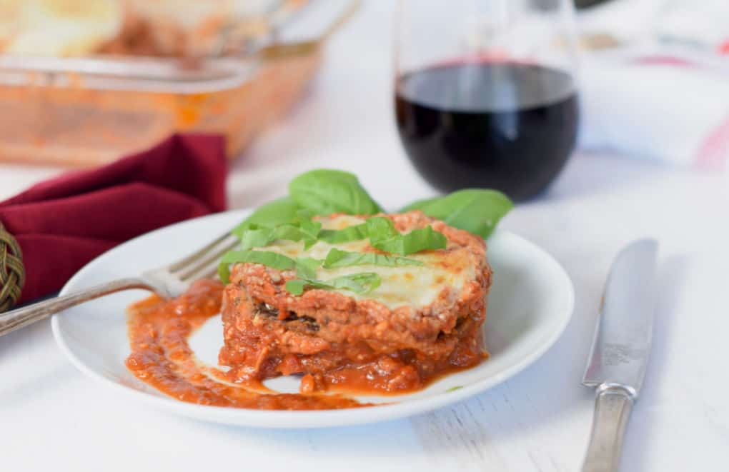 A dish of Easy Low-Fat baked eggplant parmesan with a glass of wine and the baking dish.