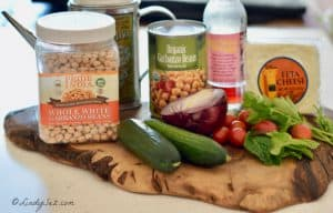 The ingredients for Mediterranean Chickpea salad sitting on a piece of wood.