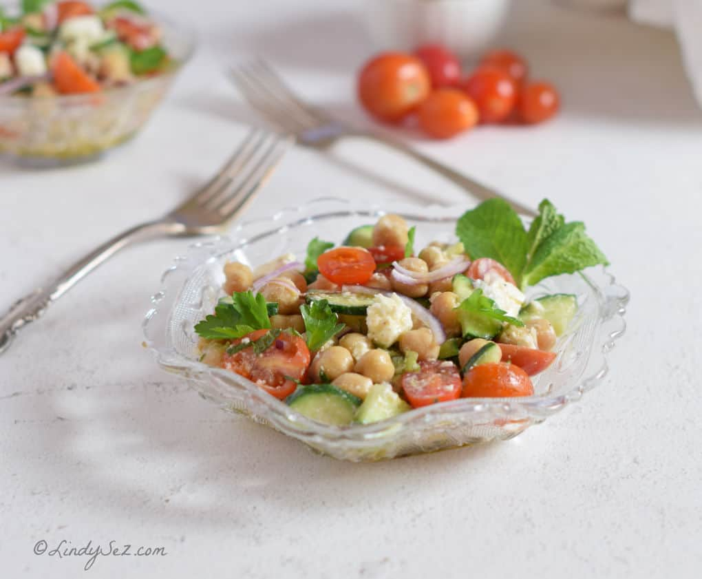 Chickpea Salad in a bowl with fresh uncut tomatoes behind.