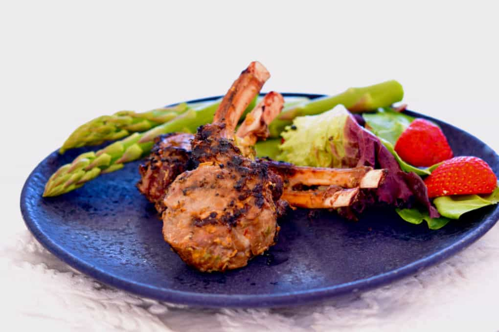 Lemongrass Grilled Lamb chops on a blue plate with fresh asparagus.