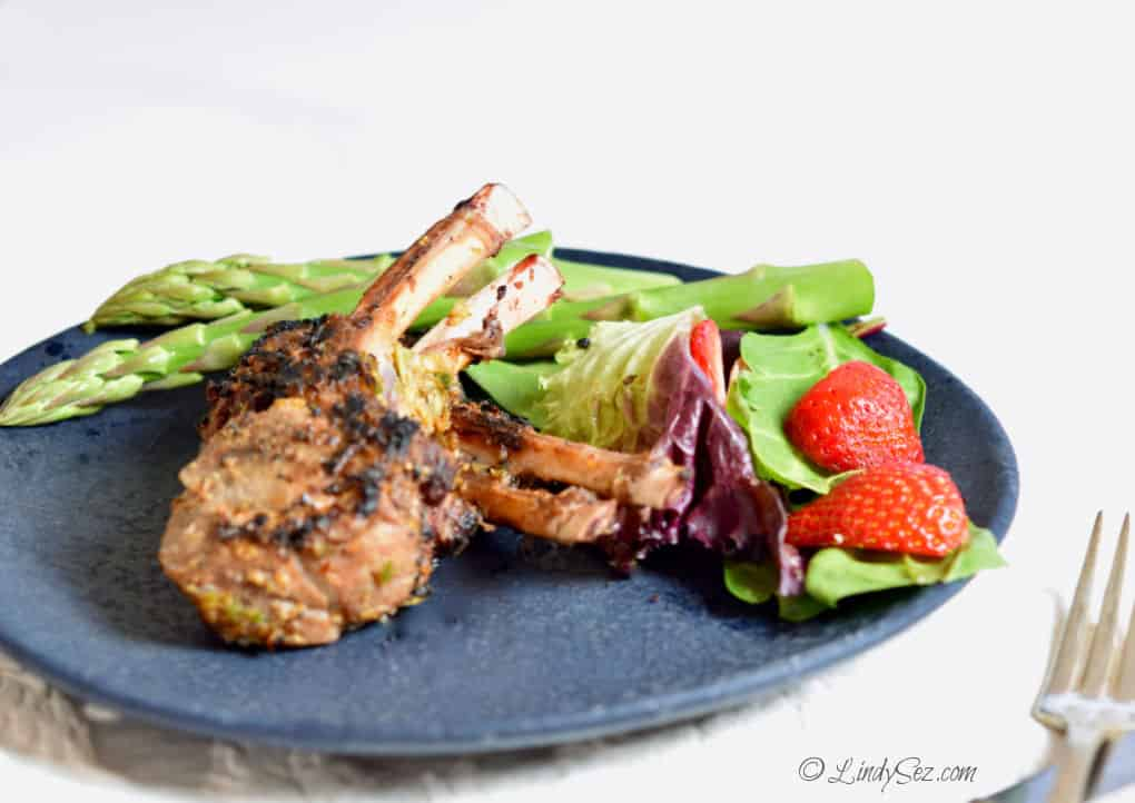 Two perfectly cooked lamb chops on a plate with green asparagus and a salad.
