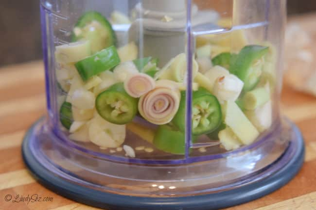 A mini-food processor with lemongrass, ginger, garlic, and Serrano peppers in it ready to be chopped.