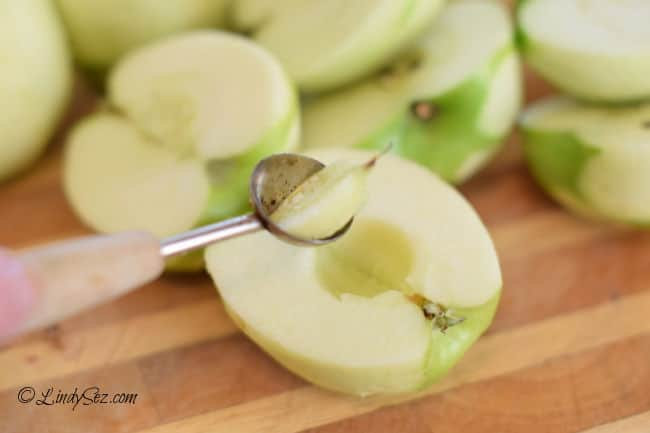 Using a melon baller to remove the core of an apple.