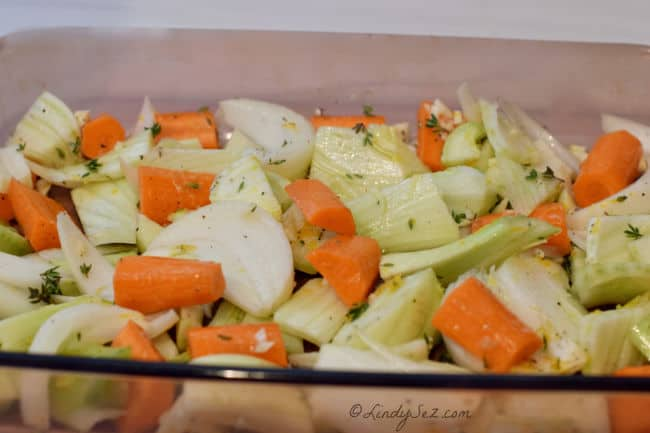 A baking dish with uncooked carrots, fennel and onions with herbs.