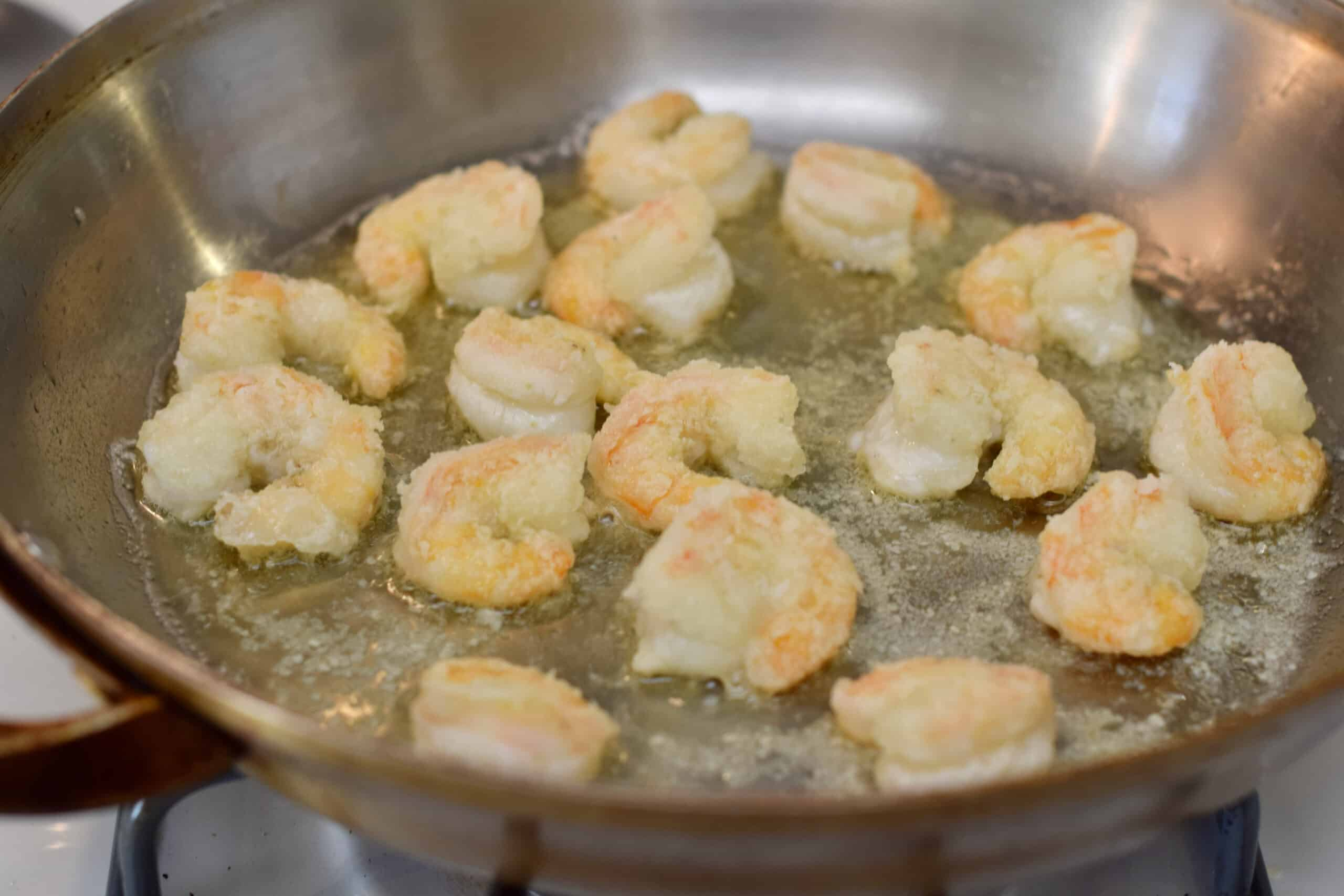 A frying pan containing some perfectly cooked crisp shrimp.
